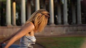 Den härliga magra flickan med lockigt hår i silverklänning justerar hennes klänning som får klar att posera under fotoperiod sida lager videofilmer