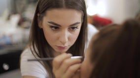 Den härliga makeupkonstnären applicerar läppstift Hand av sminkförlagen som målar kanter av den unga skönhetrödhårig manmodellen  arkivfilmer