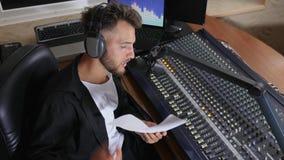 Den härliga mannen i hörlurar med mikrofon och glasögon med arket av papper läser nyheterna direkt in i mikrofonen på radiostudio lager videofilmer