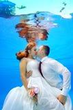 Den härliga mannen och kvinnan i bröllopsklänningar som kramar och kysser som är undervattens- i simbassängen på en bakgrund av s Arkivfoto