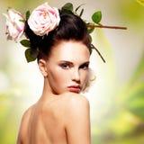 Den härliga modekvinnan med rosa färger blommar i hår Arkivfoto