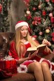 Den härliga modellen klädde som jultomten med nära en julgran royaltyfria bilder