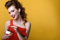 Den härliga modellen med den idérika frisyren och färgglade sminket som rymmer smaklig bakelse, dekorerade med körsbär på överkan Fotografering för Bildbyråer