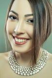 Den härliga modemodellen med makeup och smycken ser kameran Grön bakgrund, studioskott Framkallat från RÅTT, redigerat arkivbild