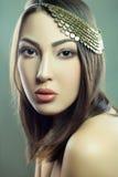 Den härliga modemodellen med makeup och smycken ser kameran Grön bakgrund, studioskott Framkallat från RÅTT, redigerat royaltyfri foto
