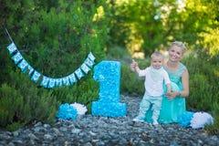 Den härliga moderdammamman i stilfulla blått klär samman med hennes son och numrerar en födelsedag parkerar in Royaltyfria Foton