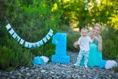Den härliga moderdammamman i stilfulla blått klär samman med hennes son och numrerar en födelsedag parkerar in Arkivfoto