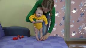 Den härliga modern med behandla som ett barn pojken som sonen gör för att stå upp övar 4K stock video