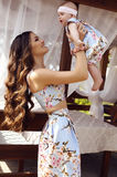Den härliga modern med långt mörkt hår som poserar med hennes lilla gulligt, behandla som ett barn i liknande klänningar Fotografering för Bildbyråer