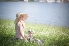 Den härliga modern och dottern sitter på gräset Royaltyfri Bild