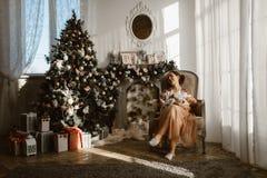 Den härliga modern sitter i fåtöljen med hennes litet behandla som ett barn bredvid spisen och nytt års träd med gåvor i arkivbild