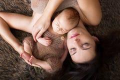 Den härliga modern som omfamnar med mjukhet och, att bry sig henne som är nyfödd royaltyfri bild