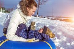 Den härliga modern spelar med hennes barn, en pojke av 4 år I vintern i den nya luften Bakgrund av snö och drivor arkivbild