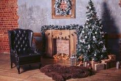 Den härliga moderna designen av rummet i mörka färger dekorerade med julgranen och dekorativa beståndsdelar Arkivfoto