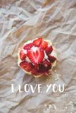 Den härliga muffin med nya jordgubbar ligger på hantverkpapperet, inskriften som jag älskar dig Royaltyfri Bild