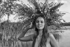 Den härliga nakna unga kvinnan med kransen har gyckel i vatten Arkivfoton