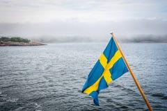 Den härliga nordiska skärgårdsommarsikten av land och ön mot havet och den disiga horisonten med svensk sjunker i förgrunden royaltyfri fotografi
