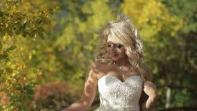 Den härliga och älskvärda bruden i parkerar Nätt och brunn-ansad kvinna Slut som skjutas upp Blondin bröllop för tappning för klä lager videofilmer