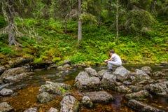 Den härliga och fridsamma platsen av en ung man som sitter och beskådar på stenen, vaggar på en skogström arkivfoto