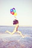 Den härliga och idrotts- brunettflickan med färgrika ballonger hoppar Royaltyfri Fotografi