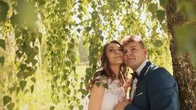 Den härliga och lyckliga bruden och brudgummen under filialerna av björkträden jublar tillsammans Kind som är fräck mot med stäng arkivfilmer