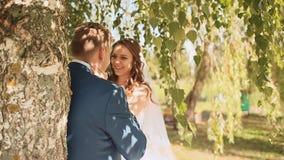 Den härliga och lyckliga bruden och brudgummen under filialerna av björkträden jublar tillsammans trycka på för händer stock video