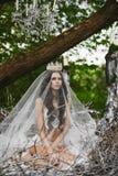 Den härliga och sexiga brunettmodellflickan, i damunderkläder och krona, sitter i ett enormt rede i den gröna skogen royaltyfri foto