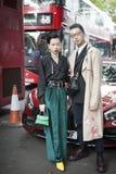 Den härliga och stilfulla a-flickan i en svart blus, en gräsplan flåsar, tappningchanelörhängen som poserar under den London mode Arkivfoton