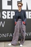 Den härliga och stilfulla a-flickan i ett svart omslag och en färgrik brun byxa poserar att posera under den London modeveckan ut Arkivfoto