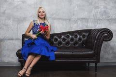 Den härliga och unga kvinnan som poserar i blått, klär på soffan Arkivbilder