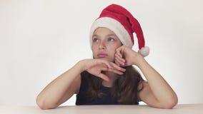 Den härliga olyckliga flickatonåringen i en Santa Claus hatt uttrycker känslomässigt en eftertänksam sorgsenhet på det vita bakgr arkivfilmer