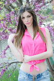 Den härliga passformdamen mellan blomningträdet i lilor färgar Royaltyfri Fotografi