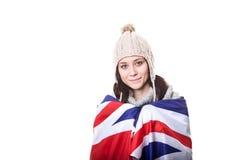 Den härliga patriotiska livliga unga kvinnan med amerikanska flaggan rymde i hennes utsträckta händer som framme står av Arkivbilder