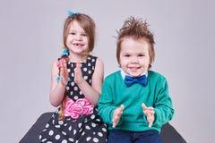 Den härliga pysen och flickan applåderar deras händer och leende Fotografering för Bildbyråer