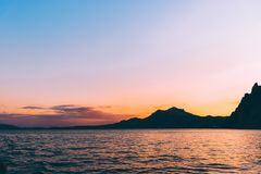 Den härliga röda och purpurfärgade solnedgången på Black Sea med konturn av vaggar Karadag, Krim Royaltyfria Foton