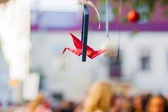 Den härliga röda origamikranen animerade mer på gallerit Origamin sträcker på halsen flyg i vit bakgrund royaltyfria foton