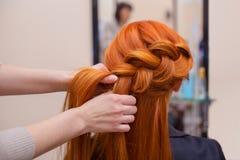 Den härliga rödhåriga flickan med långt hår, frisör väver en fransk flätad tråd, i en skönhetsalong arkivfoton