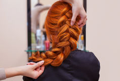 Den härliga rödhåriga flickan med långt hår, frisör väver en fransk flätad tråd, i en skönhetsalong royaltyfri foto