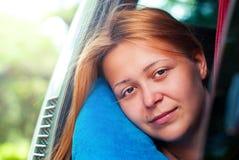 Den härliga rödhåriga flickan ser ut ur bussfönstret, medan resa Royaltyfri Fotografi