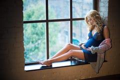 Den härliga rödhåriga gravida flickan sitter på fönstret Royaltyfri Foto