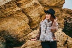 Den härliga rödhåriga kvinnan i en hatt och ett halsdukanseende på bakgrunden av vaggar Turism vilar, livsstilen Utrymme f?r fotografering för bildbyråer