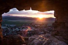 Den härliga Rasnov staden som igenom ses ett liitlefönster av Rasnovs fästning royaltyfria bilder