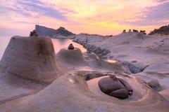 Den härliga reflexionen av rosig soluppgånghimmel på den geologiska Yehliu kusten parkerar med ljusstaken vaggar bildande Royaltyfri Bild
