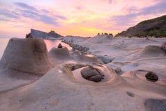 Den härliga reflexionen av rosig soluppgånghimmel på den geologiska Yehliu kusten parkerar med ljusstaken vaggar bildande Arkivfoton