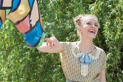 Den härliga romantiska blonda flickan i retro stil spelar med statyn Arkivbild