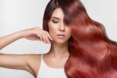 Den härliga rosa färg-haired flickan i flyttning med krullar perfekt hår och klassiskt smink Härlig le flicka fotografering för bildbyråer