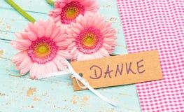 Den härliga rosa gruppen av blommor och kortet med det tyska ordet, Danke, hjälpmedel tackar dig Royaltyfria Foton
