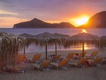 Den härliga rosa orange solnedgången på den Agios Georgios Pagon stranden på den Korfu ön, Grekland med solparaplyer tömmer sunbe royaltyfria bilder