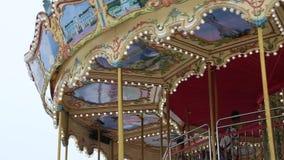 Den härliga runda karusellen för barn` s rotera i ett nöjesfält arkivfilmer