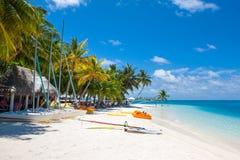 Den härliga sandiga stranden i skuggan av gömma i handflatan för vattensport Arkivbilder